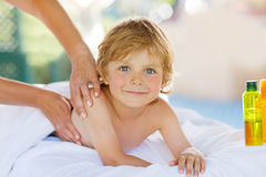 Adorable little blond kid relaxing in spa with having massage royalty free stock image