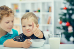 Adorable little blond kids eating cereals for breakfast or lunch. Stock Photos