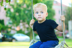 Adorable little blonde boy having fun at the playground. Adorable little blonde boy having fun at the playground at park Royalty Free Stock Photos