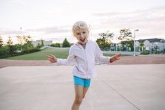 Adorable little blonde Caucasian girl child making funny silly face. Happy childhood. Portrait of cute adorable little blonde Caucasian girl child making funny royalty free stock photos