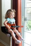 Adorable little blonde curly-hair Caucasian toddler girl with blue eyes is holding an ukulele guitar, sitting on the high chair , stock image