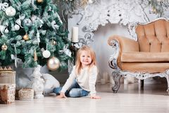 Adorable little blonde girl in a blue jeans sitting on a floor near christmas tree and looking on toy. Adorable little blonde girl in a white dress sitting on a Stock Images