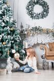 Adorable little blonde girl in a blue jeans sitting on a floor near christmas tree and looking on toy. Adorable little blonde girl in a white dress sitting on a Stock Photography