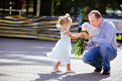 Adorable little blonde girl gives daddy peonies stock images
