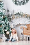Adorable little blonde girl in a blue jeans sitting on a floor near christmas tree and looking on toy. Adorable little blonde girl in a white dress sitting on a Stock Photo