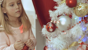 Adorable little blue-eyed girl decorates the Christmas tree Royalty Free Stock Photo