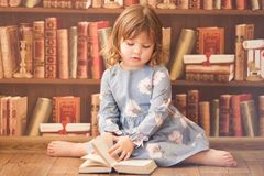 Adorable little bookworm girl reading books. Adorable little bookworm girl reading books, preschool child in the library, retro style. vintage indoor photo stock photography