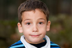 Adorable little boy. Portrait of an adorable little boy outdoors looking at the camera with a serious expression Royalty Free Stock Photo