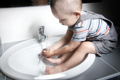 Adorable  little boy. At the age of two in a striped T-shirt  looking at the flow of water in the sink and washing her hands and feet in the sink Stock Photos
