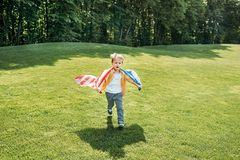 Adorable little boy with american flag running on grass. In park royalty free stock photography