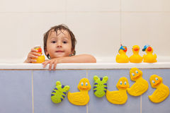 Adorable little boy in bathtub with his rubber duckies Stock Images