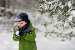 Adorable little boy, blowing snowflakes outside in a snowy day Royalty Free Stock Photography