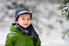 Adorable little boy, blowing snowflakes outside in a snowy day Stock Photos