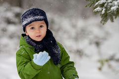 Adorable little boy, blowing snowflakes outside in a snowy day Royalty Free Stock Images