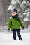 Adorable little boy, blowing snowflakes outside in a snowy day Stock Photo