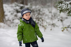 Adorable little boy, blowing snowflakes outside in a snowy day Royalty Free Stock Photo