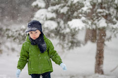 Adorable little boy, blowing snowflakes outside in a snowy day Royalty Free Stock Image