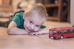 Adorable little boy with blue eyes lays on the ceramic floor with toy red bus. Blonde hair, green t-shirt.