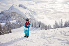 Adorable little boy with blue jacket and a helmet, skiing in win Royalty Free Stock Image