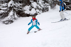 Adorable little boy with blue jacket and a helmet, skiing in win Royalty Free Stock Photo