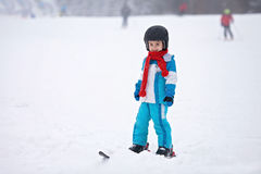Adorable little boy with blue jacket and a helmet, skiing Stock Images