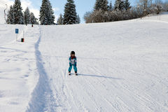 Adorable little boy with blue jacket and a helmet, skiing Royalty Free Stock Photography