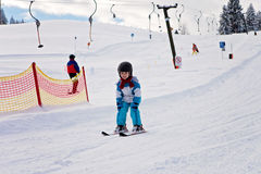 Adorable little boy with blue jacket and a helmet, skiing Royalty Free Stock Images