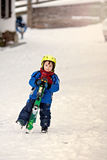 Adorable little boy with blue jacket and a helmet, skiing Stock Photos