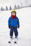 Adorable little boy with blue jacket and a helmet, skiing Royalty Free Stock Image