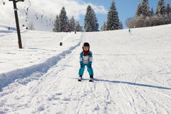Adorable little boy with blue jacket and a helmet, skiing Stock Photography