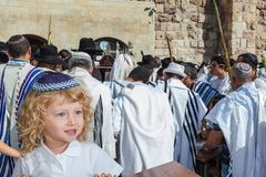 Adorable little boy in blue skullcap. Adorable little boy with long blond curls and blue eyes in blue skullcap. He stands at Western Wall of Temple. The Jewish Stock Photo