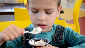 Adorable little boy in a businessman`s business suit in a hurry eating ice cream at restaurant during lunch. stock video footage