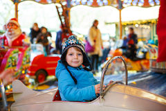 Adorable little boy on a carousel at Christmas funfair or market Royalty Free Stock Image