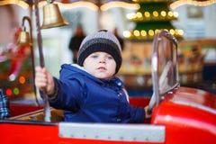 Adorable little boy on a carousel at Christmas funfair or market Stock Photos