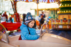 Adorable little boy on a carousel at Christmas funfair or market Stock Photography