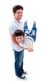 Adorable little boy carried by his father. Against a white background Stock Images