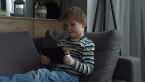 Preschool kid using digital tablet for playing game. Adorable little boy in casual outfit relaxing on couch, playing on line game on digital tablet pc at home stock video footage