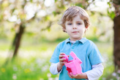 Adorable little boy celebrating Easter holiday and making egg hu Royalty Free Stock Photos