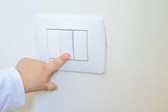 Adorable little boy child turning on the white light-switch with his finger Stock Image