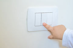 Adorable little boy child turning on the white light-switch with his finger of little hand, new generation concept Stock Photo