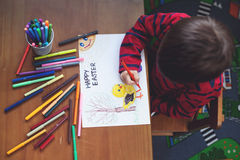 Adorable little boy, drawing picture for easter Royalty Free Stock Images