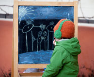 Adorable little boy, drawing summer picture with chalk on a boar Royalty Free Stock Image