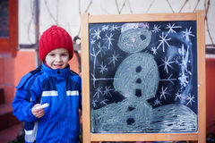 Adorable little boy, drawing winter picture with chalk Royalty Free Stock Image