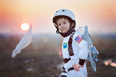 Adorable little boy, dressed as astronaut, playing in the park w. Ith rocket and flag, dreaming about becoming an astronaut Royalty Free Stock Photo