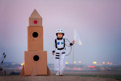 Adorable little boy, dressed as astronaut, playing in the park w Stock Images