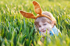 Adorable little boy with Easter bunny ears playing in green gras Royalty Free Stock Photos