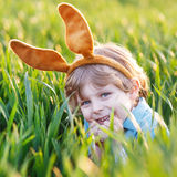 Adorable little boy with Easter bunny ears playing in green gras Stock Images