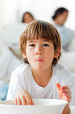 Adorable little boy eating chips on the floor Royalty Free Stock Images