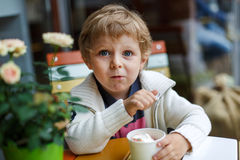 Adorable little boy eating frozen yoghurt ice cream in cafe Stock Images
