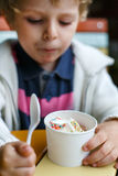 Adorable little boy eating frozen yoghurt ice cream in cafe Royalty Free Stock Images